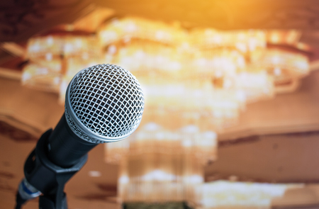 Close-up of microphone in conference seminar for speech or concert hall with event blur light background