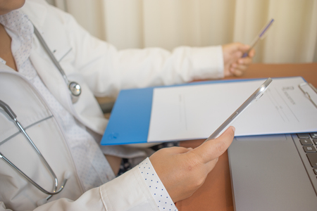Doctor working smart phone and laptop computer on desk, prescription clipboard on table in  hospital office, Healthcare and medically concept, selective focus Stockfoto
