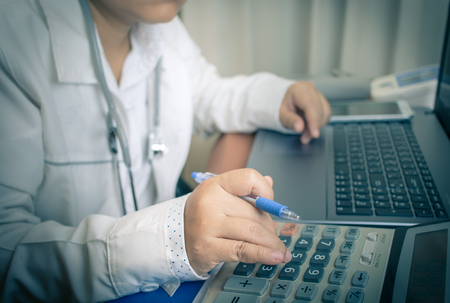 Doctor holding pen with Stethoscope for analyzing calculator laptop on Laptop computer, table in hospital Healthcare and medically concept, selective focus