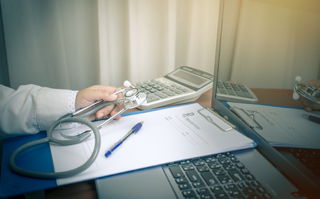 Doctor holding medical prescription paper clipboard with Stethoscope for patient note calcuator on Laptop computer, table in hospital Healthcare and medically concept, selective focus