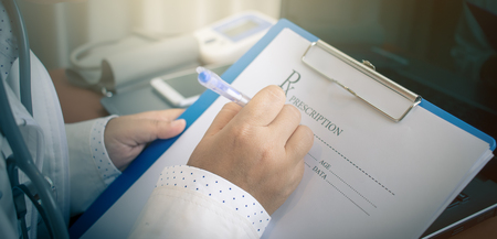 Young Doctor writing medical prescription paper clipboard with Stethoscope for patient note on Laptop computer table in hospital Healthcare and medically concept, selective focus