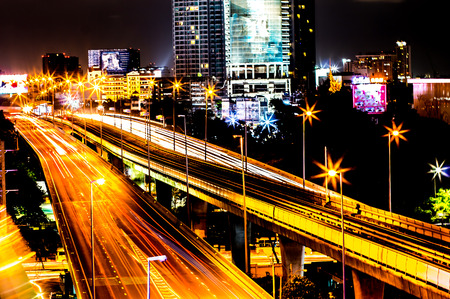 Colorful of city modern buildings night and road light abstract background, decorated with de-focus bokeh lights cities offices of reflecting building in Bangkok Thailand. Stock Photo