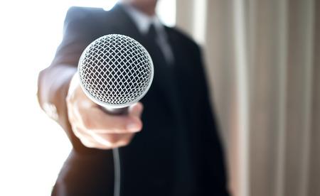 Aziatische Slimme zakenmanentoespraak en het spreken met microfoons in seminarieruimte of sprekend conferentiezaallicht met microfoons en keynote. Spraak is een vocale vorm van communicatie tussen mensen. Stockfoto