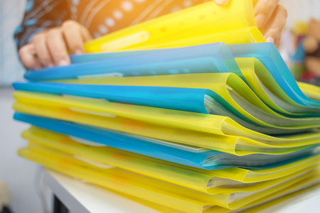 Asian Businesswoman hands working in many documents Stacks of folders in office for Annual Report files, Piles of color folder close annual budget, business busy concept.
