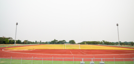 Red treadmill, track running and football field at the stadium with  grass.