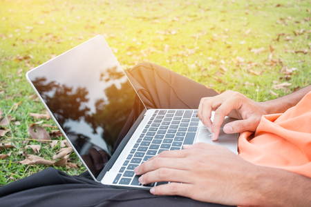 Top view of young man sitting in park on green grass with laptop computer, student studying searching information at outdoors. Copy space for text. E-Learning concept