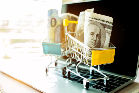 Amerikaanse dollars, JPY-geld in karretje op laptop toetsenbord. Idee van geld wisselen online winkelen, online winkelen is een vorm van e-commerce, consumenten om goederen te kopen van direct verkoper via internet. Stockfoto - 91452203