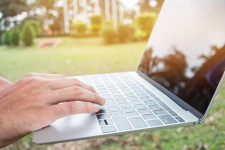 Studenten jonge man met behulp van laptopcomputer in park op groen gras in school, student studeert het zoeken van informatie op buitenshuis. Ruimte voor tekst kopiëren. E-learning concept Stockfoto - 91465489