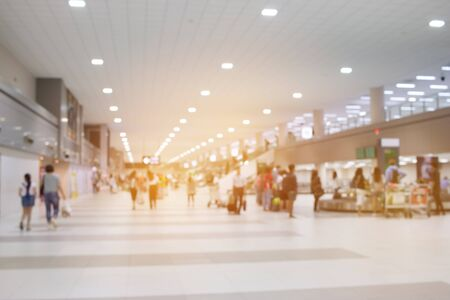 Large group people arriving and traveling carries luggage walking in airport terminal building waiting for check in. blurred crowd of traveler people on background. Traveling concept.