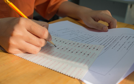 Uniform School Asian students taking exams writing answer optical form with pencil in high school classroom, view of having exams in class on seat rows, Education test and literacy concept. Stockfoto