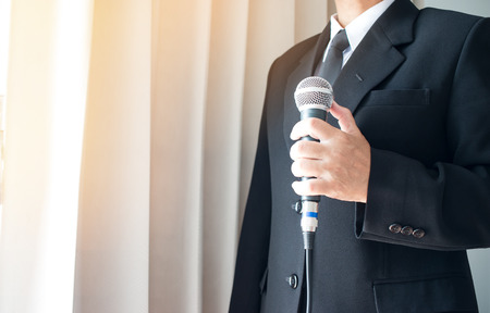 Smart businessman speech and speaking with microphones in seminar room or talking conference hall light with microphones and keynote. Speech is vocalized form of communication humans.