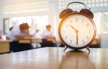 Closeup of Retro alarm clock with ten o'clock on table teacher in blur students exams classroom. Time is indefinite continued progress of existence. Education concept, selective focus.