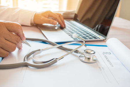 Doctor's writing and working on laptop computer, writing prescription clipboard with record information paper folders on desk in hospital or clinic, Healthcare and medical concept. Focus stethoscope