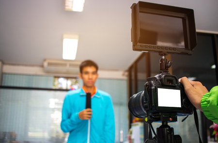 Man on set Video camera, camcorder interviews, operator working for record speaker or Presenter in office, blak white screen. Interview is conversation where questions are asked and answers given