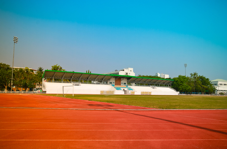 Red treadmill, track running at the stadium with green grass on blue sky Stockfoto