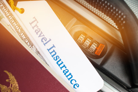 Travel Insurance tag on suitcase near numeric combination lock,passport and US Dollar. Travel Insurance is intended cover medical expenses,cover lost luggage flight cancellation or accident Reklamní fotografie