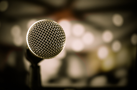Retro Microphones on front stage in pub bar or restaurant. Classic sing a song in evening and night show concert light bokeh background.