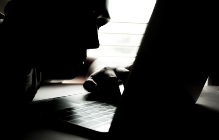 Hackers with black mask using hands of anonymous typing code on keyboard of laptop for remotely reach and receiving personal information online networking, Internet Crime Payment Security Concept Stockfoto