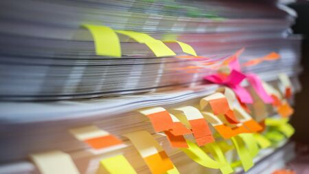 Paper stack, Pile of unfinished documents with post it on office desk related to business functions. Stack of business papers for Annual Report files. Business offices concept.