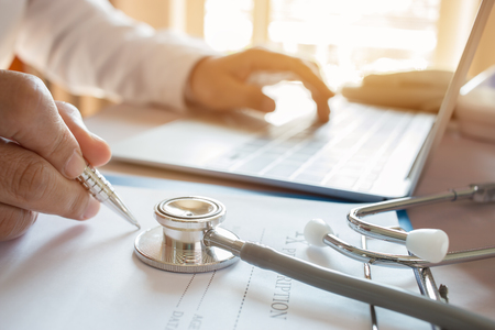 Schreiben Medizindoktors auf Laptop im Ärztlichen Dienst Fokusstethoskop auf Vordergrundtabelle im Wirtszentrum Stethoskop ist akustisches medizinisches Gerät für Auskultation und hört interne Töne des menschlichen Körpers Standard-Bild