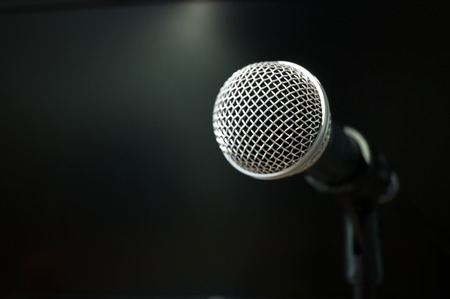 Retro Microphones on front stage in pub bar or restaurant. Classic sing a song in evening and night show on black light background.