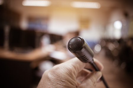 Microphones in seminar room, talking speech in conference hall light with microphone and keynote. Speech is vocalized form of communication humans, Blurred of audience in meeting room, vintage tone Stockfoto