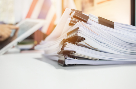 Paper stack, Pile of unfinished documents on office desk related to business functions. Stack of business papers for Annual Report files on blur National flag,use tablet. Business offices concept Stockfoto