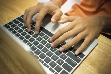 Male hands using modern laptop on keyboard in home office on wooden table.