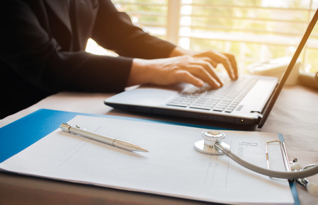 Doctors working on laptop computer, writing prescription clipboard with record information paper folders on desk in hospital or clinic, Healthcare and medical concept. Focus on stethoscope Stockfoto