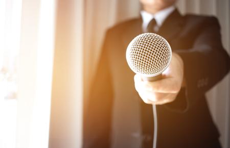 ビジネスマンにインタビューマイクを提出するジャーナリスト。スマートレポーターがカンファレンスでのプレゼンテーションでマイク付きインタビューとスピーチを行い、ビジネスセミナーコンセプト 写真素材 - 91833350