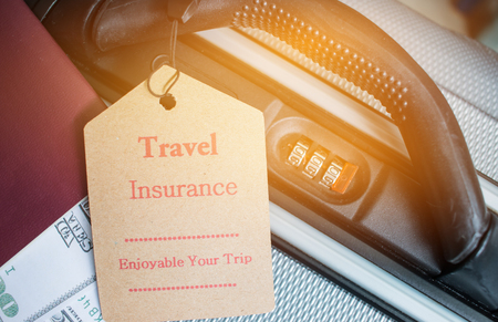 Travel Insurance tag on suitcase near numeric combination lock, passport and US Dollar. Travel Insurance is intended cover medical expenses,cover lost luggage flight cancellation or accident