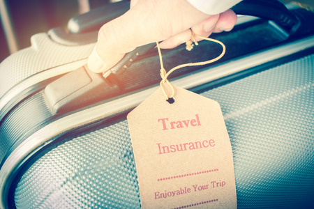Hands holding Travel Insurance tag on Suitcase safety with letters enjoyable your trip on bag light blurred background, that is intended cover medical expenses, trip cancellation or flight accident. Stockfoto - 91725945