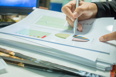 Businessman Preparing reports papers with graphs, charts on Stacks of documents files for finance in office. Piles of unfinished document achieves with paper clip. Concept of Business Annual Report.