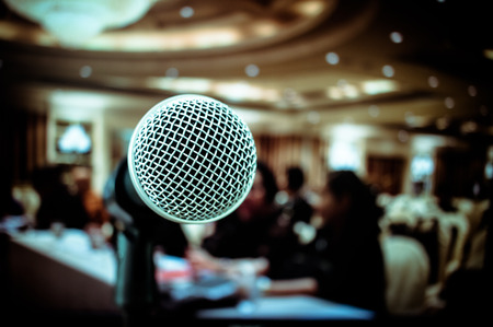 Microphones on front stage in seminar room, for talking speech in conference hall light with microphone and keynote, blur light of audiences meeting room background, vintage tone