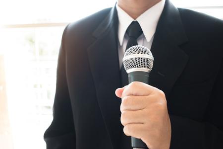 Slimme zakenmanentoespraak en sprekend met microfoons in seminarieruimte of sprekend conferentiezaallicht met microfoons en keynote. Spraak is een vocale vorm van communicatie tussen mensen.