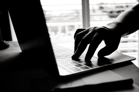 Handen van anonieme hackers typen code op het toetsenbord van de laptop voor het op afstand bereiken en ontvangen van persoonlijke informatie online netwerken, Internet Crime Payment Security Concept, Silhouette zwart wit Stockfoto - 92881612