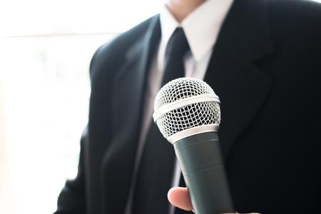Slimme zakenmanentoespraak en sprekend met microfoons in seminarieruimte of sprekend conferentiezaallicht met microfoons en keynote. Spraak is een vocale vorm van communicatie tussen mensen. Stockfoto - 92881613
