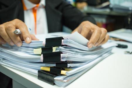 Mãos da mulher de negócios que trabalham em pilhas de arquivos de originais para finanças no escritório. Documentos de relatório de negócios ou pilhas de documentos inacabados são obtidos com o clipe de papel preto. Conceito de Relatório Anual de Negócios Foto de archivo