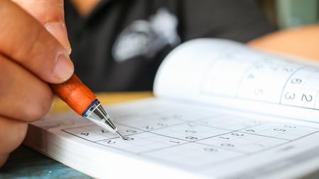 De student probeert sudoku met kleurenpotlood op te lossen als hobby bij openlucht Stockfoto - 92850243