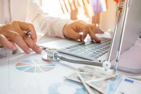 Arts die aan laptop computer met rapportanalyse en geld over Gezondheidszorgkosten en prijzen in medisch hoofdkantoor werkt. Focus stethoscoop op tafel. Gezondheidszorgbegroting en bedrijfsconcept