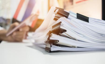 Papierstapel, stapel onafgewerkte documenten op bureau met betrekking tot zakelijke functies. Stapel handelspapieren voor jaarverslagen op nationale vlag vervagen, slimme telefoon gebruiken. Bedrijfskantoren concept Stockfoto