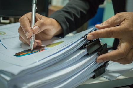 Zakenman die rapportendocumenten met grafieken, grafieken op Stapels documentendossiers voorbereiden voor financiën in bureau. Stapels onafgemaakt document worden behaald met paperclip. Concept van zakelijk jaarverslag.