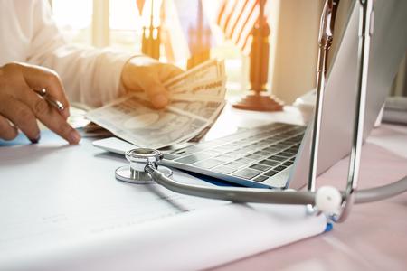 Geneeskundedokter die JPY-geld houdt voor kosten in de gezondheidszorg en vergoedingen in een medisch hoofdkantoor. Focusstethoscoop is een akoestisch apparaat voor auscultatie, waarbij interne geluiden worden beluisterd. Gezondheidszorg budget concept Stockfoto - 92931196
