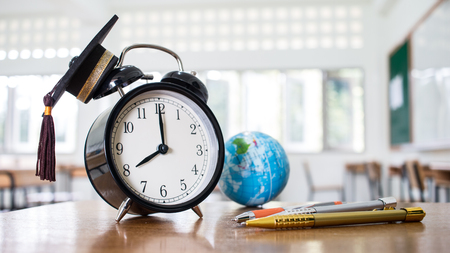 Retro alarm clock 2 o'clock, left side on table teacher with earth global map, Graduation cap, pen in blur empty classroom. Time is indefinite continued progress of existence. Education exams concept.