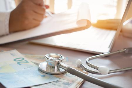 Geneeskundedokter die JPY-geld houdt voor kosten in de gezondheidszorg en vergoedingen in een medisch hoofdkantoor. Focusstethoscoop is een akoestisch apparaat voor auscultatie, waarbij interne geluiden worden beluisterd. Gezondheidszorg budget concept Stockfoto