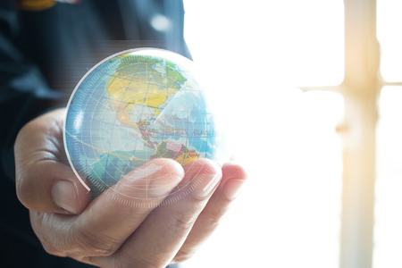 Businessman holding Earth globe model in hands. Concept for global business, communications, politics or environmental for learning world wide in online market. Stockfoto