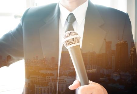 Mensen uit het bedrijfsleven spreken of spreken met microfoons over investeringen Onroerend goed in de vergaderzaal in de conferentiezaal. Onroerend goed is eigendom bestaande uit landgebouwen, Blur nacht stad achtergrond.