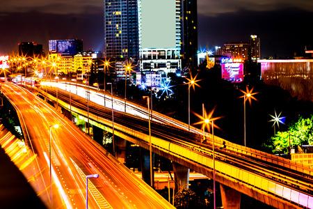 Kleurrijk van nacht van stads de moderne gebouwen en weg lichte abstracte die achtergrond, met de-nadruk bokeh lichten van stedensteden van het weerspiegelen van de bouw in Bangkok Thailand wordt verfraaid.