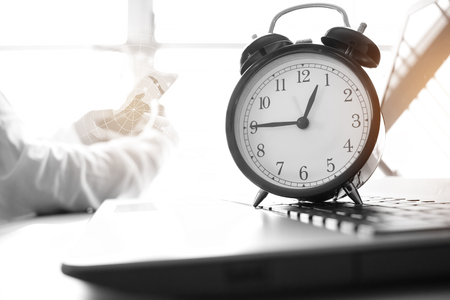 Alarm clock with Radar background on computer, businessman using smart phone background. Concept of Times Studies lead to success in life, black and white color.