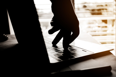 Cyber crime hand reaching out through laptop computer and attack signifying in internet theft while using online banking, Payment Security Concept. Anonymous Hacked in Black